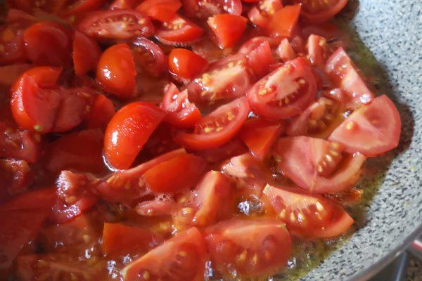 Nel frattempo soffriggete l'altro spicchio di aglio in camicia per 30 secondi al massimo in 5 cucchiai di olio e.v.o. dopo di che toglietelo. Aggiungete la passata di pomodoro i pomodorini tagliati in 4 o a metà, mescolate e fate cuocere a fuoco vivace per circa 5 minuti.