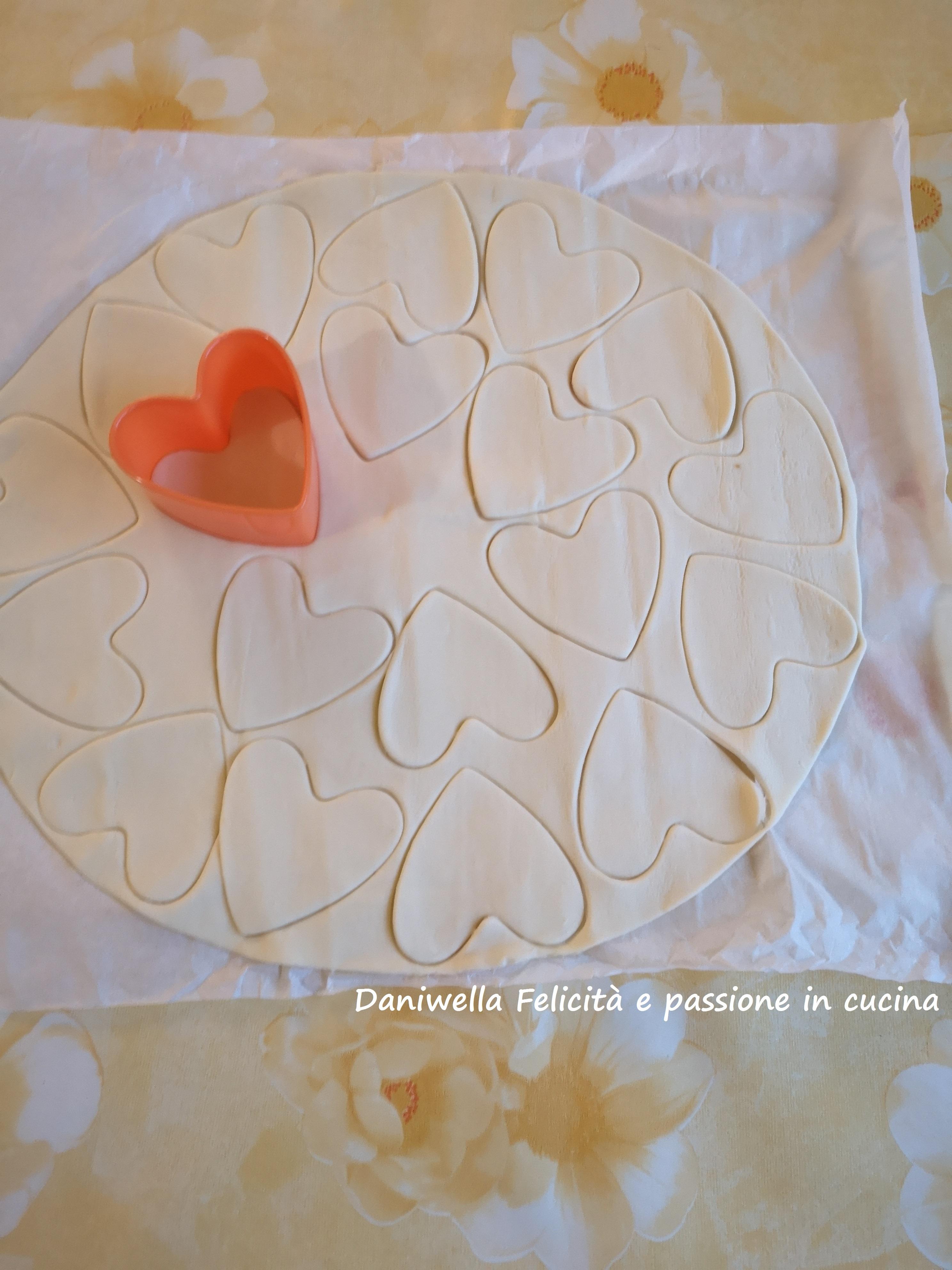 Srotolate il rotolo di pasta, con lo stampino intagliate la pasta a forma di cuore e disponeteli su una leccarda ricoperta di carta forno.