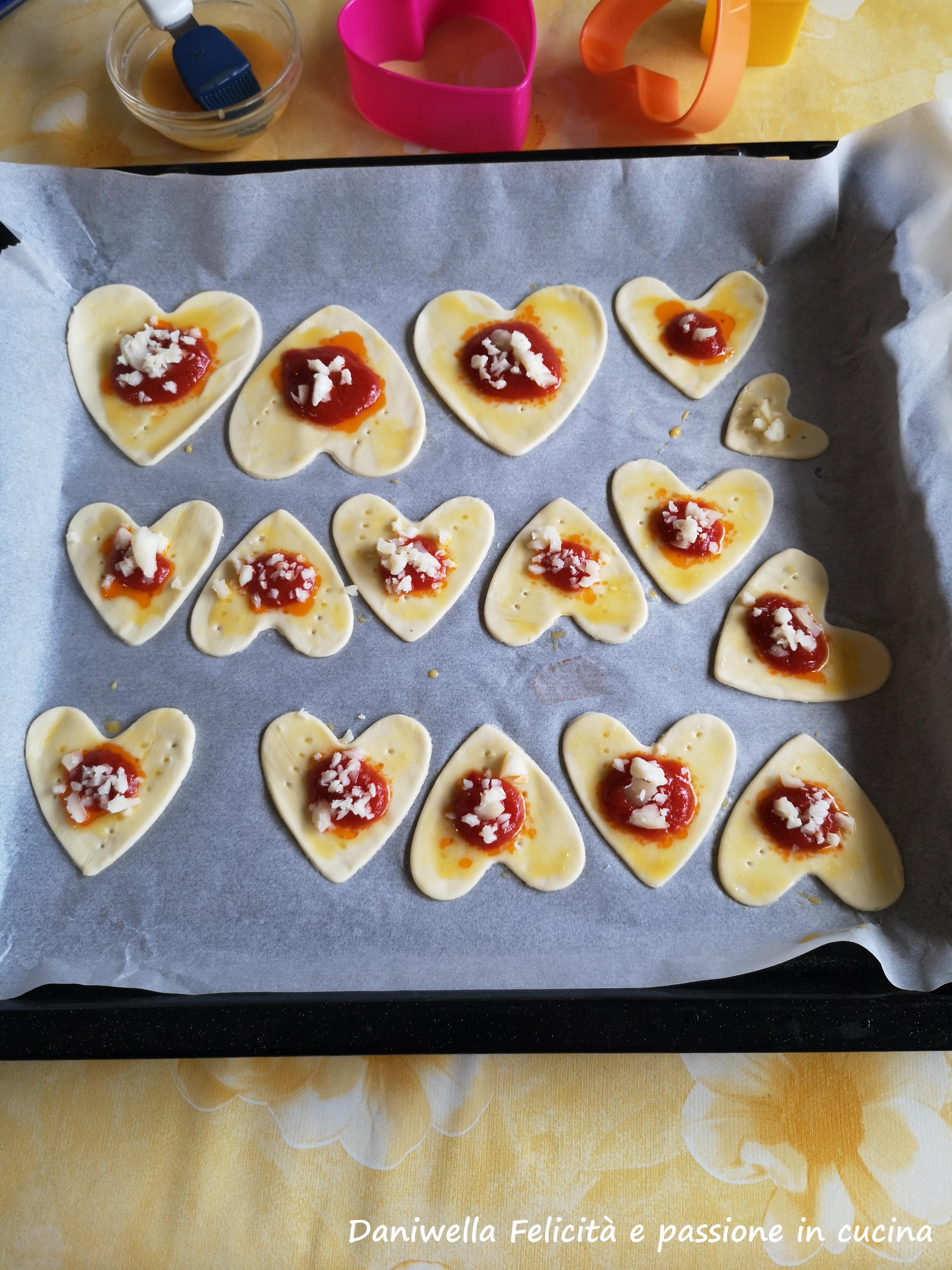 Su ogni cuore mettete 1 cucchiaino circa di passata di pomodoro e  i cubetti di formaggio.