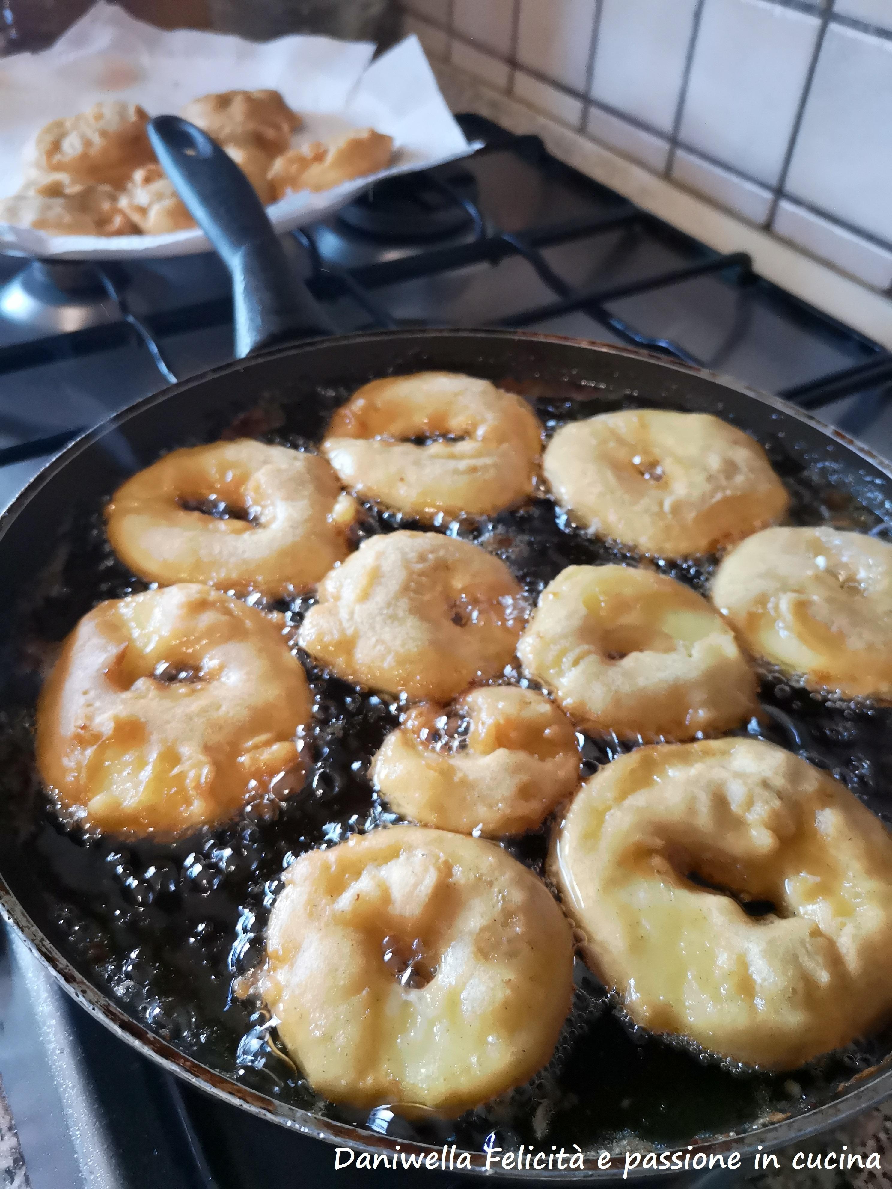 Passati i 30 minuti, scaldate l'olio e portatelo ad una temperatura di 175°. Tuffate ogni fettina di mele nella pastella e friggetele nell'olio caldo, fatele dorare da entrambi i lati.