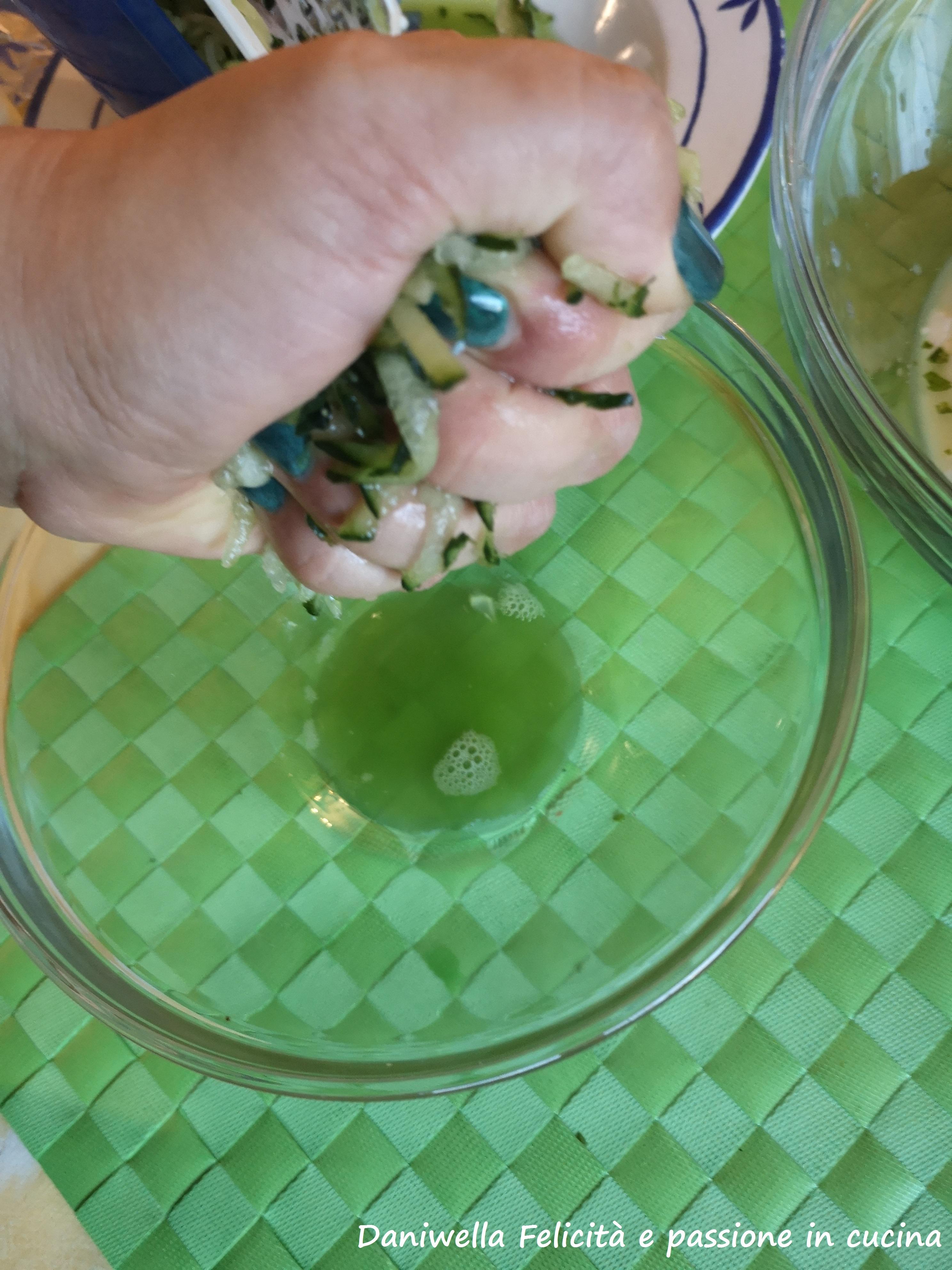 Strizzate il più possibile tra le mani il cetriolo grattugiato. Cercate di eliminare quanto più possibile l'acqua di vegetazione. Il cetriolo si deve ridurre notevolmente.