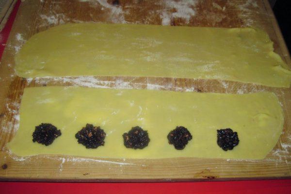 Stendete la pasta in sfoglie sottili e procedete come per fare i ravioli, mettendo 1 cucchiaino di ripieno sulle strisce di pasta, ripiegandole su se stesse. Disponete i mucchietti a 4 cm di distanza dal bordo e separati tra loro 5 cm.
