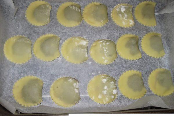 Tagliate ora i caciunitt a mezzaluna con una rondella o un bicchiere. Man mano che li fate poneteli sopra un vassoio ricoperto di carta forno spolverato di farina.