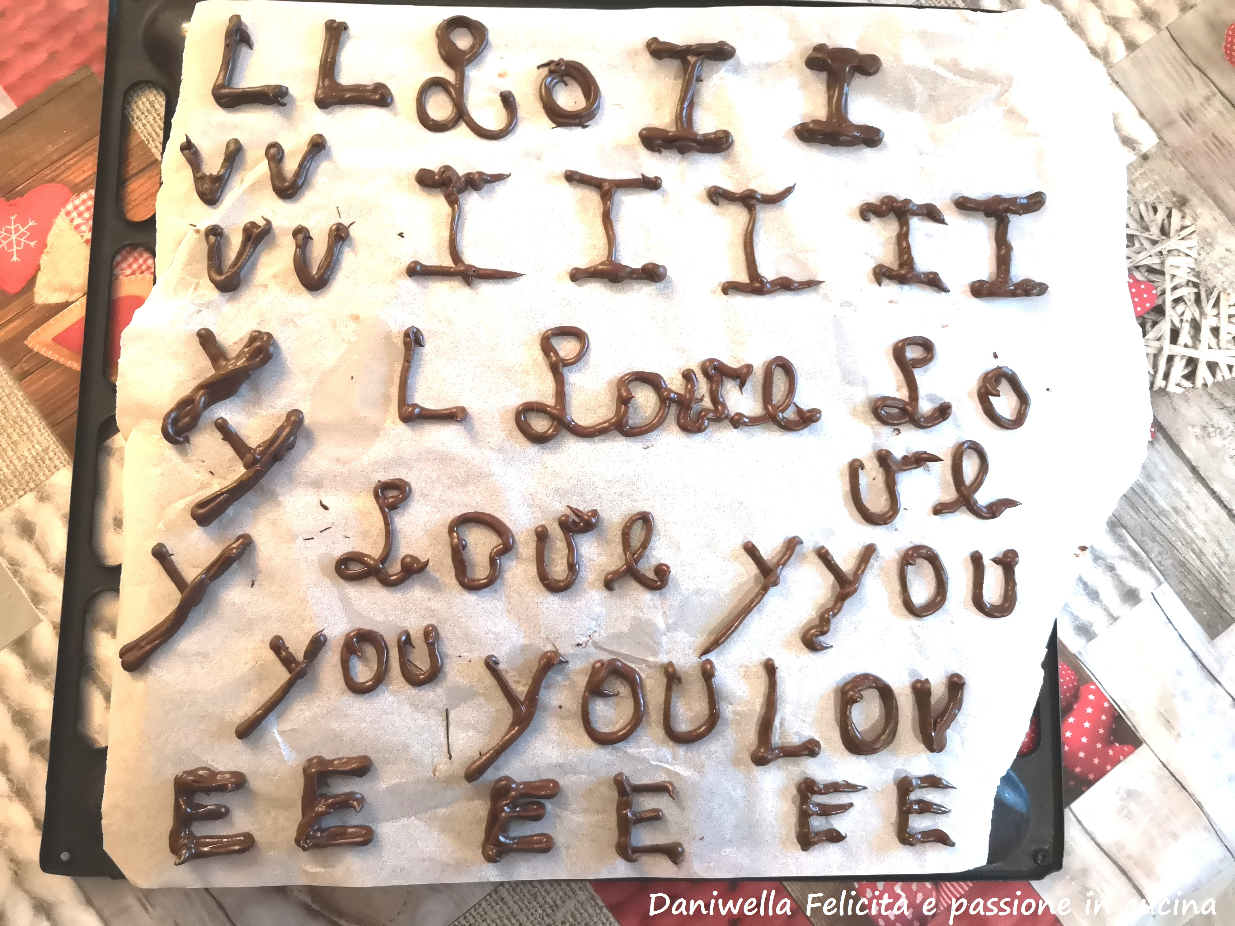 Sciogliete il cioccolato fondente e ricoprite la torta. Con il cioccolato avanzato formate le lettere della scritta I LOVE YOU e aspettate che si raffreddino completamente prima di decorare la torta.