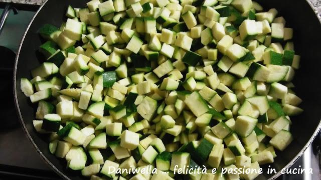 Imburrate e infarinate uno stampo per plumcake lungo 30 cm. Lavate, mondate e tagliate a cubetti le zucchine. Rosolate lo spicchio d'aglio in camicia e schiacciato nell'olio caldo per 30 secondi dopo di che toglietelo. L'olio si sarà insaporito e l'aglio non rischierà di bruciarsi. Aggiungete le zucchine con un pochino di sale, saltatele in padella per una decina di minuti circa, fin tanto che si ammorbidiscano.