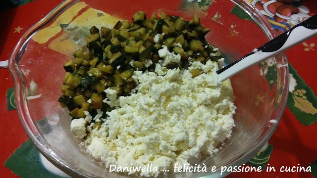 Incorporate la feta sbriciolata, le zucchine, il parmigiano, le foglioline di menta e prezzemolo tritati a coltello e mescolate.