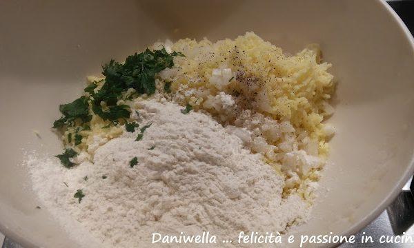 In una ciotola unite il purè di patate, il formaggio, l'uovo,  80 g di farina, la cipolla, il prezzemolo, sale e pepe. Mescolate bene per amalgamare gli ingredienti.