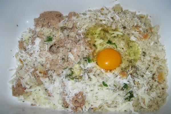 In una ciotola capiente mettete il lesso e il pane tritati la mollica di pane sbriciolata, i formaggi grattugiati, gli aromi secchi in polvere, 1 spicchio d'aglio e il prezzemolo tritati e amalgamate per bene.