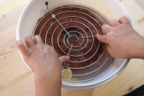 Versate la bagna calda dentro una ciotola e inzuppateci per qualche minuto il babà. Aiutatevi con una gratella. Dopo di che con molta attenzione scolate la bagna e rovesciate la torta posizionandola sopra la gratella. Saltate il primo passaggio se vi sembra difficoltoso e passate al successivo.