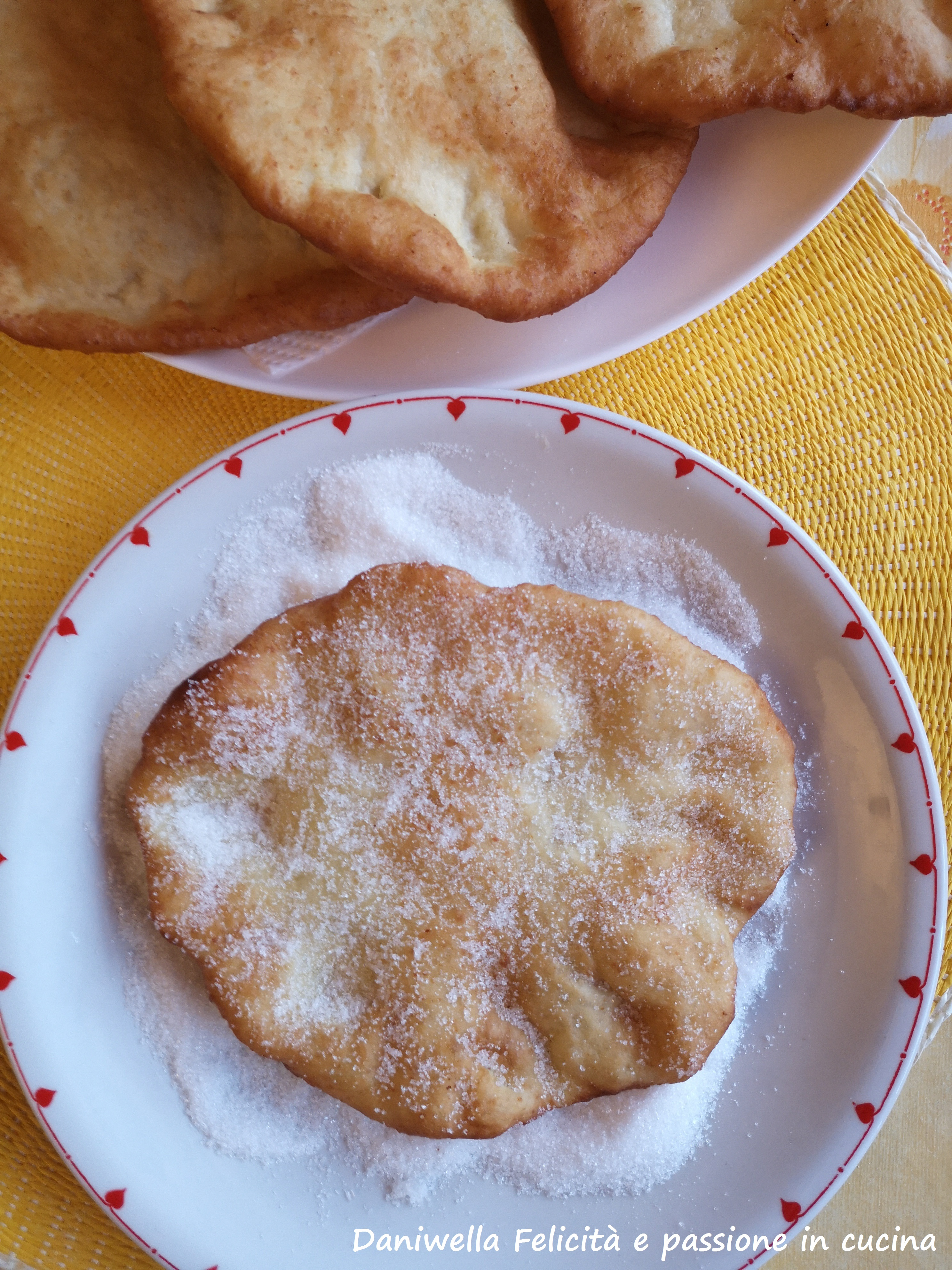 Scolate ogni frittella su carta assorbente e dopo passatele nello zucchero semolato.
