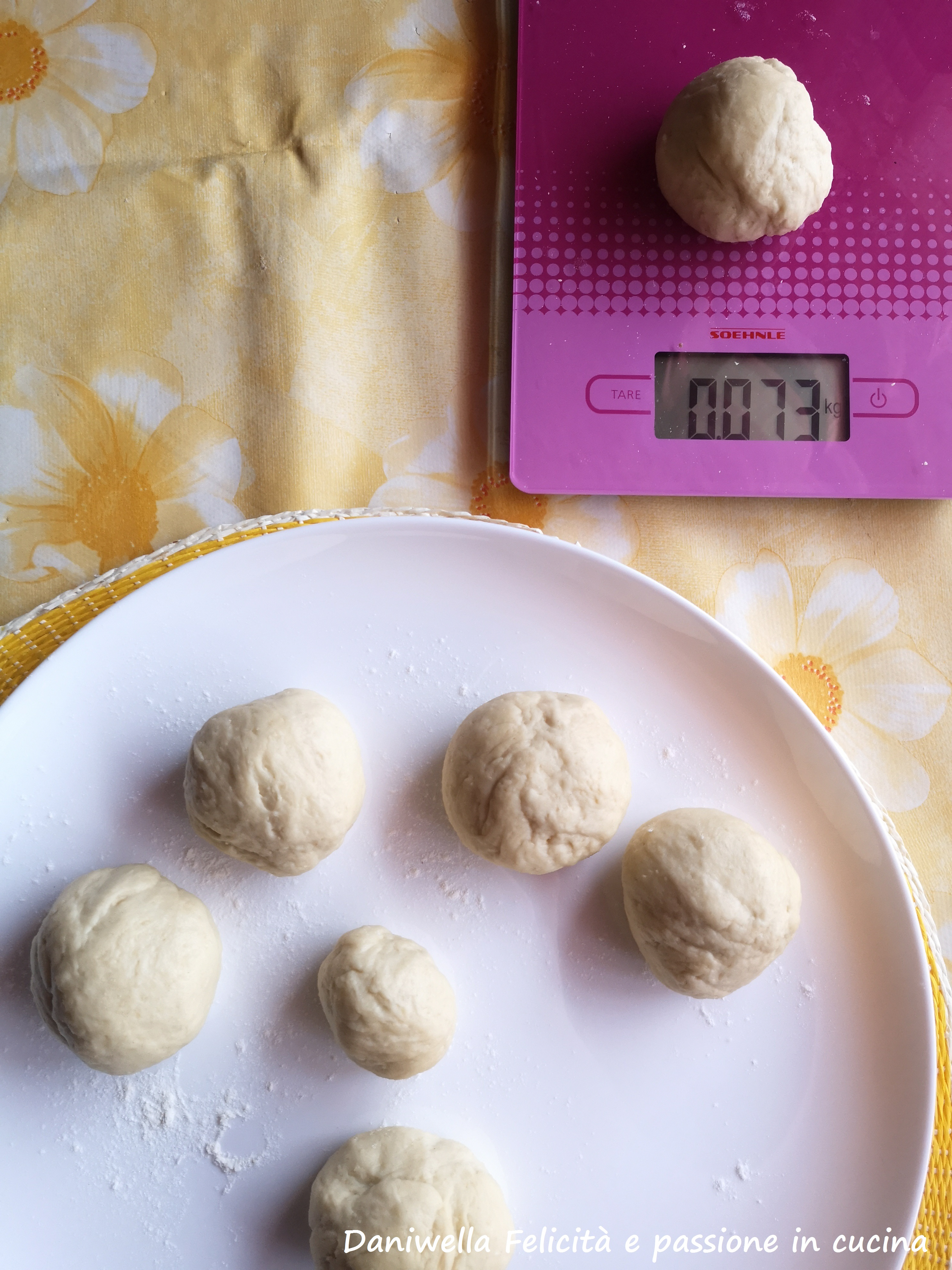 Riprendete l'impasto, sgonfiatelo e dividetelo in 5/6 pezzi di 60/70 g l'uno, formate delle palline e mettetele a lievitare su di un piatto spolverato di farina coperto con un canovaccio per per 30/40.