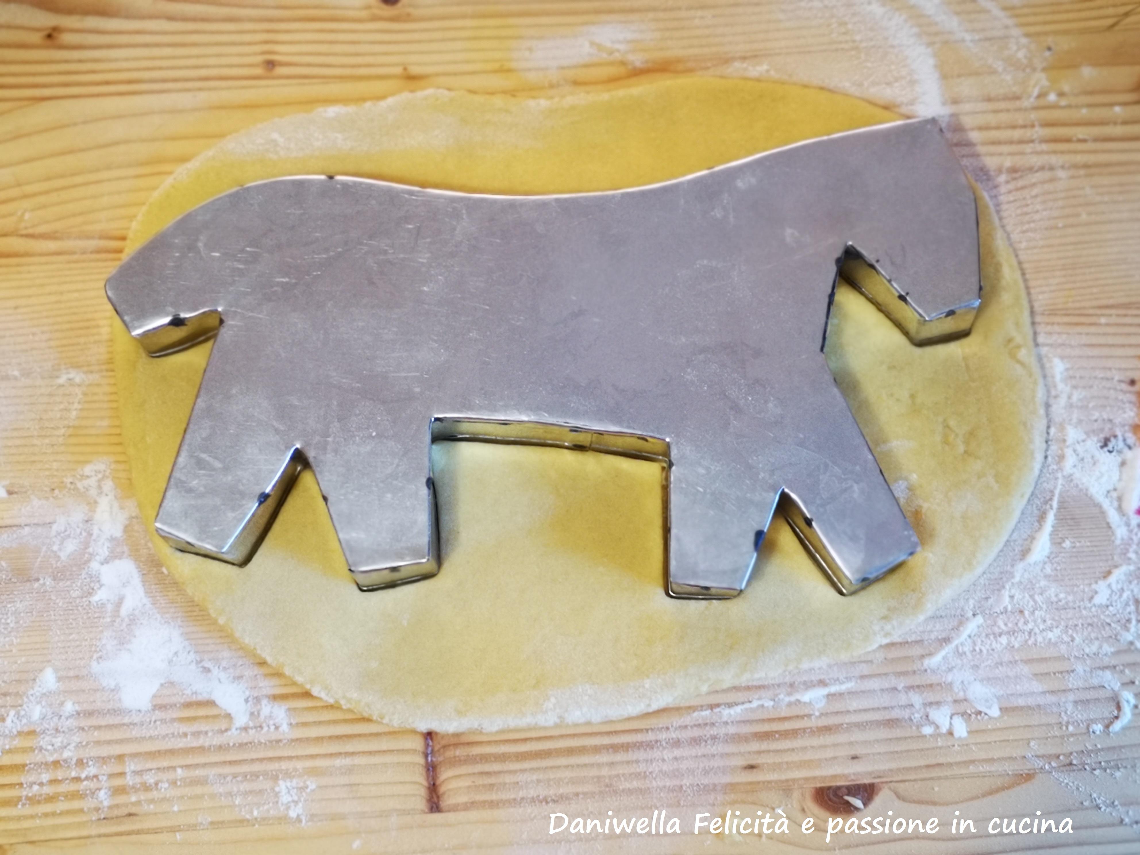 Premete con forza per imprimere le forme. Con delicatezza tirate su lo stampo e trasferite la pupa e il cavallo su una leccarda coperta da un foglio di carta forno.