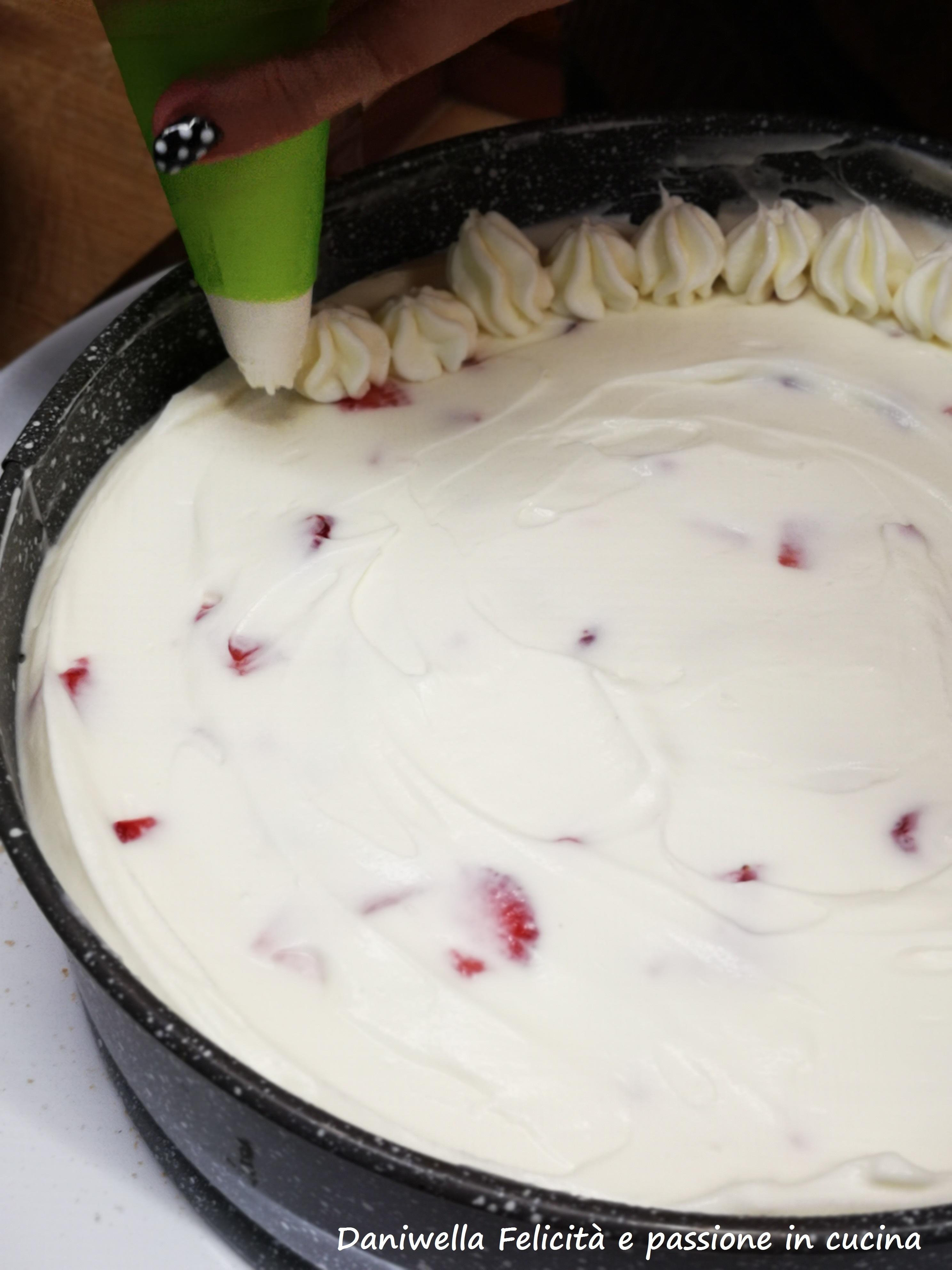 Con la crema e le fragole avanzate prepariamo la decorazione finale che renderà la torta bella e superlativa anche alla vista. Con l'aiuto di un sac a poche e una bocchetta a stella fate dei ciuffetti tutto intorno, staccandovi leggermente dalla parete dello stampo. Mettete la torta in frigorifero.