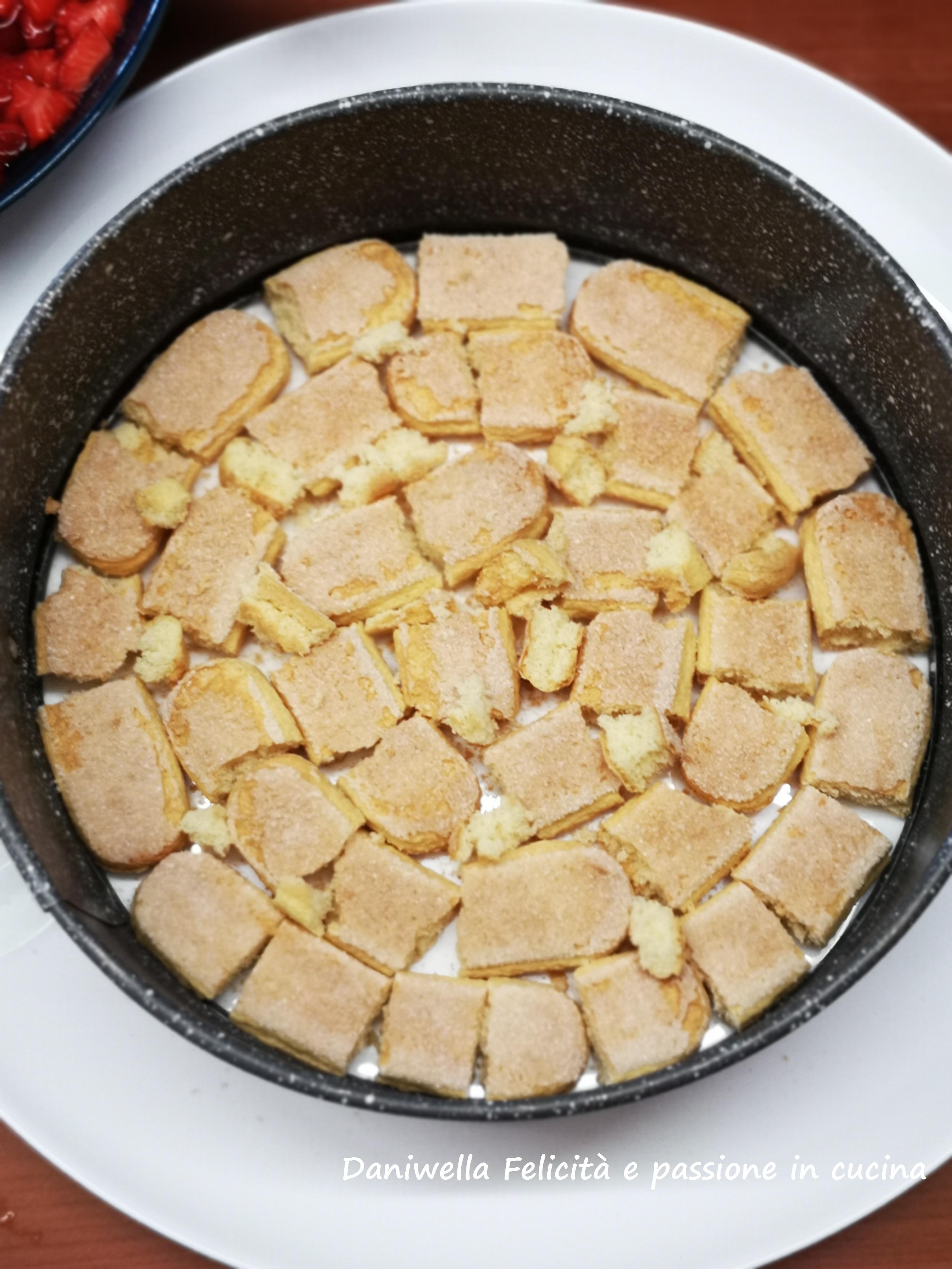 Prendete uno stampo a cerniera di cm 22 di diametro e sostituite il fondo con un piatto da portata. Chiudete la cerniera e poggiatelo sul piatto e cominciate a formare gli stati alternati. La torta avrà 2 stati e ogni strato conterrà 100 g di savoiardi. Prendete i biscotti e con le mani rompeteli in tre parti, partendo dall'esterno ricoprite tutta la superficie. Se vedete che ci sono dei buchini sbriciolateci sopra qualche pezzettino fino a riempirli a tappo.