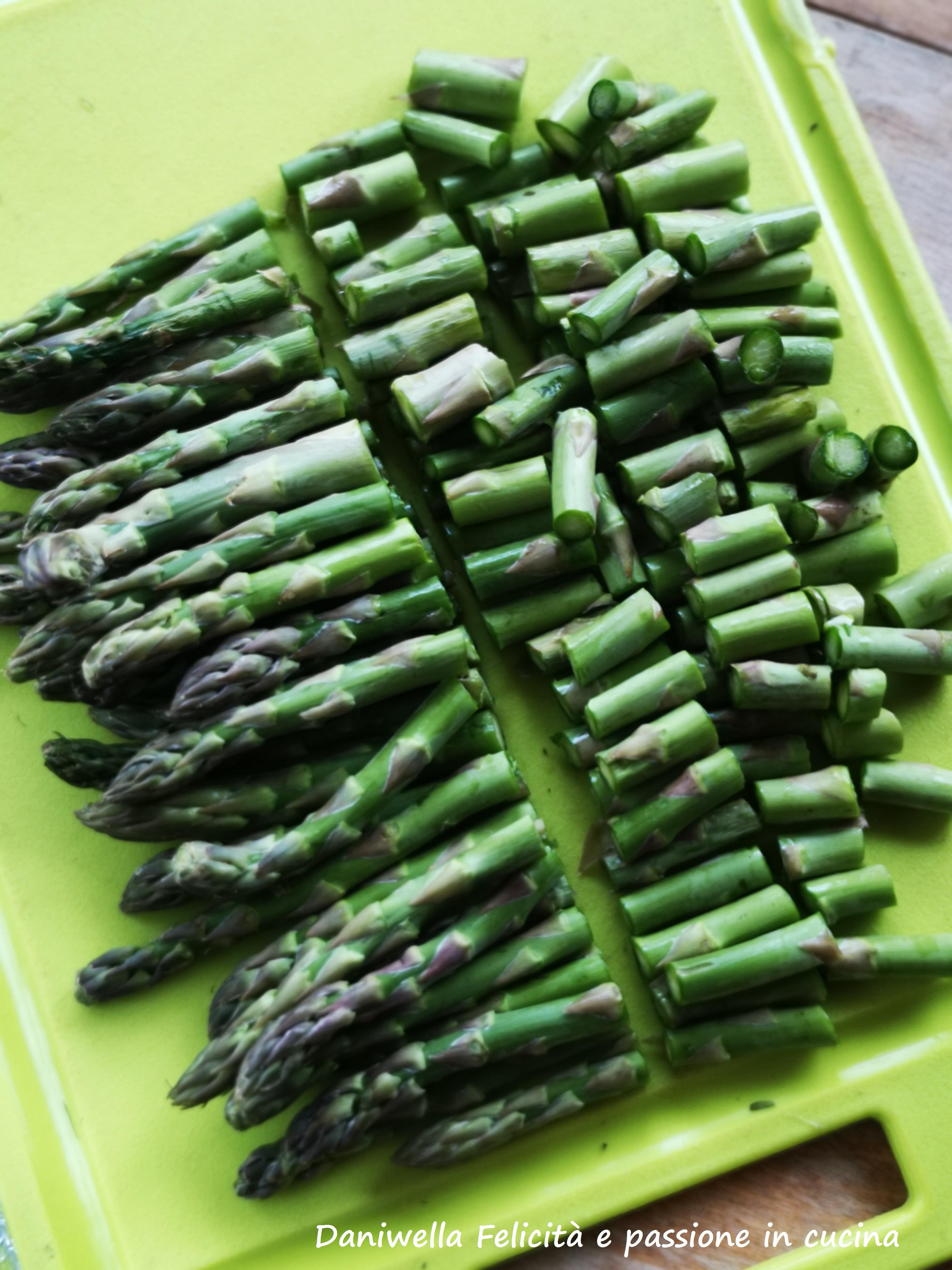 Lavate gli asparagi sotto l'acqua corrente. Poggiateli su un tagliere. Tagliate i gambi in 3/4 parti e lasciate intere le punte che metterete da parte.