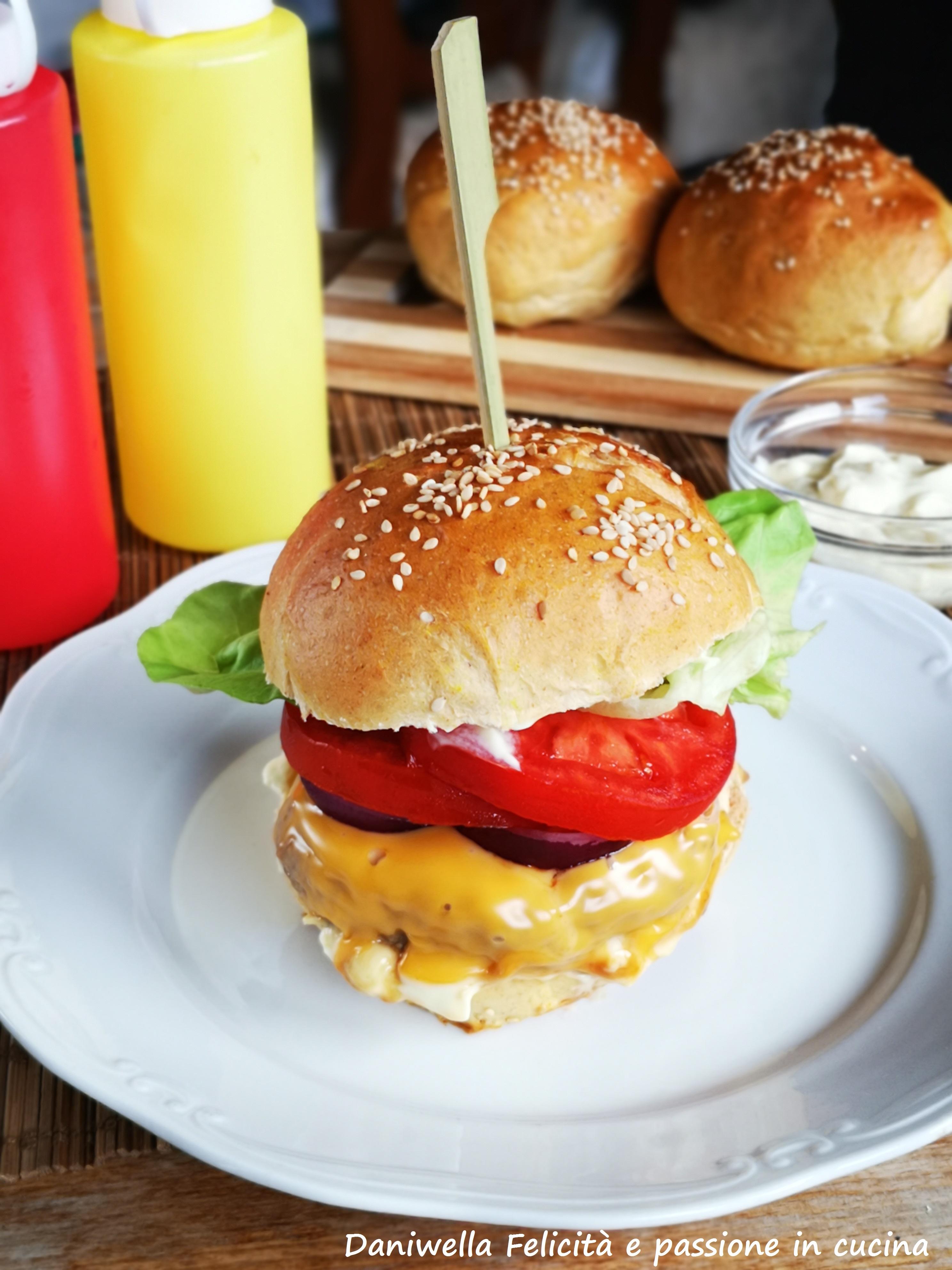 Spalmate sulla corona del pane e sulla base la maionese. Componete il vostro cheeseburger. Partendo dal basso – pane – maionese – hamburger – fettina di formaggio cheddar – cipolla rossa – pomodoro – maionese – pane.