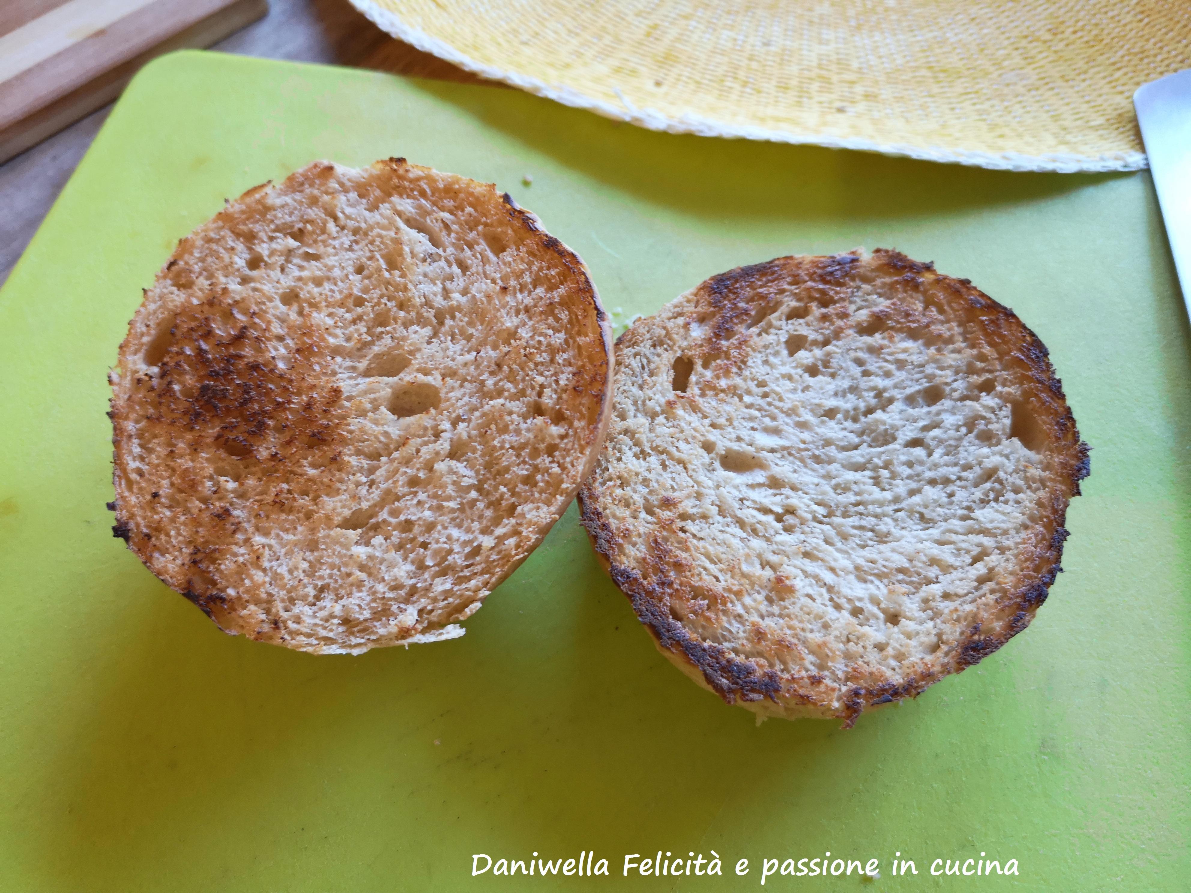 Tagliate a metà i due panini e grigliate leggermente le due parti su una piastra calda. Per facilitare la tostatura spennellate un velo di burro sul pane.