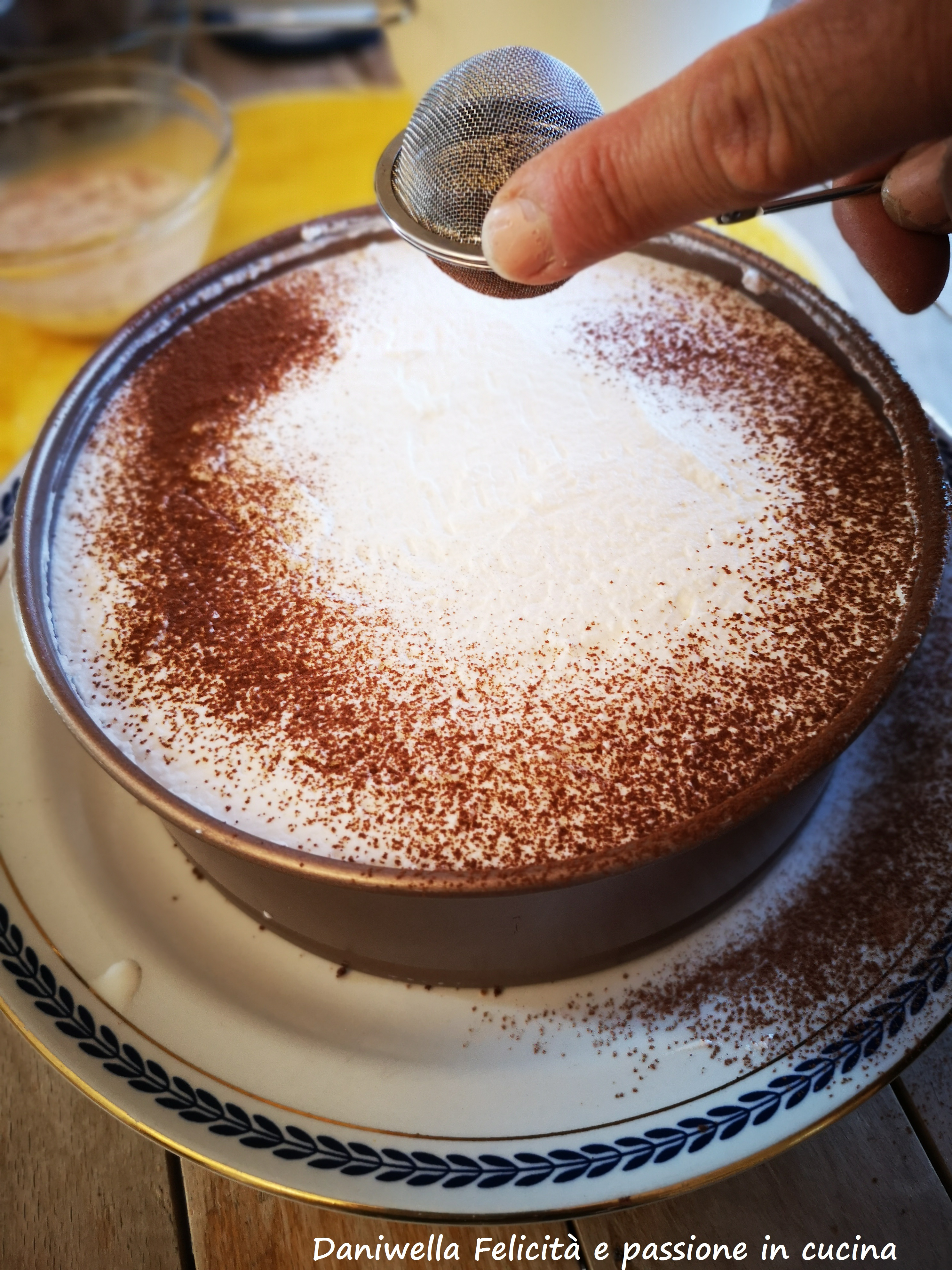 Ricoprite con l'ultimo strato di panna. Spolverizzate la superficie con il cacao amaro. Pulite i bordi del piatto dal cacao amaro caduto in eccedenza e mettete in frigorifero a rassodare.