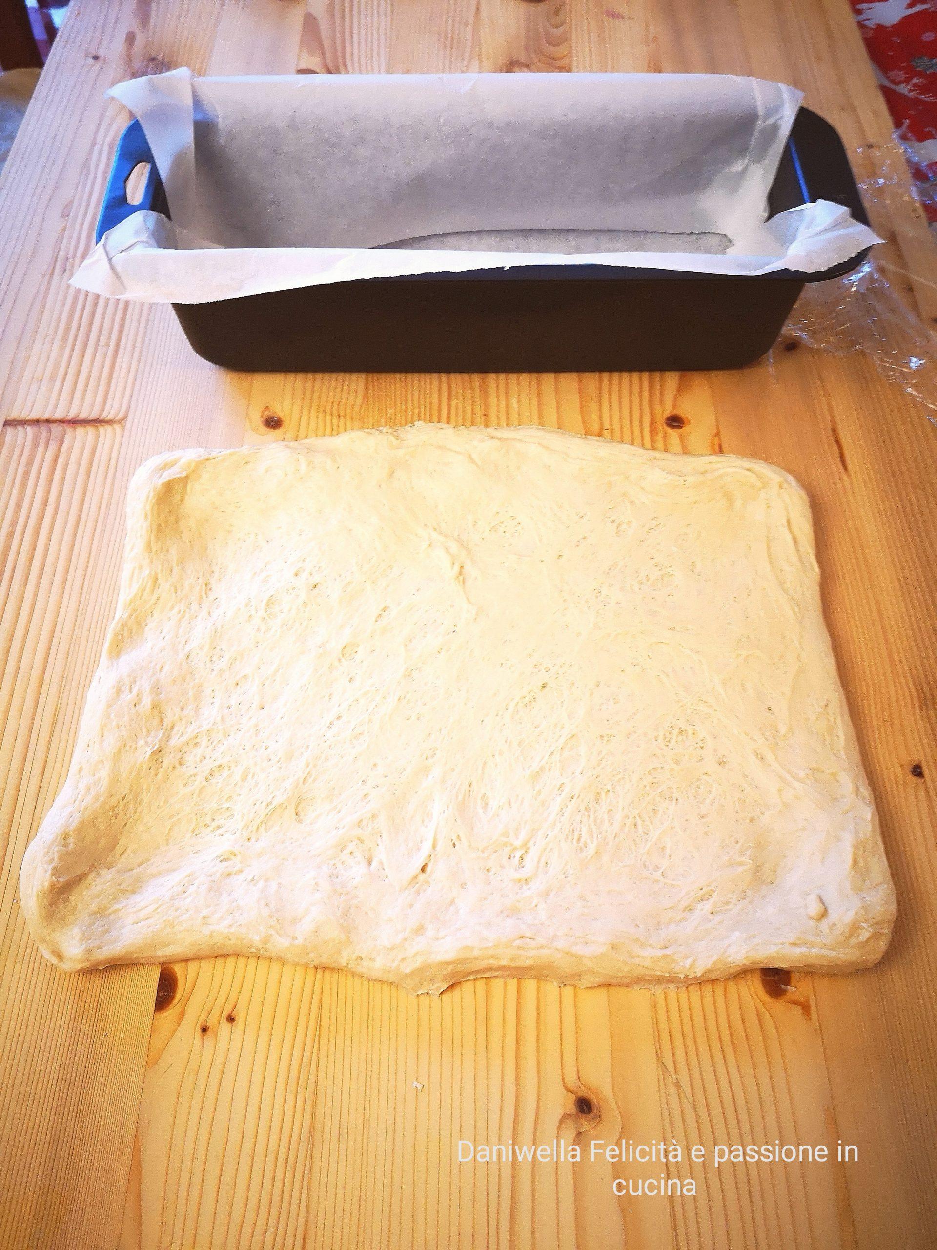 Rivestite di carta forno uno stampo da plumcake delle dimensioni di cm 30 x 10 x 8. Rovesciate l'impasto lievitato su una spianatoia, apritelo con le mani e realizzate un rettangolo. Una dimensione del rettangolo deve essere pari del lato lungo dello stampo.