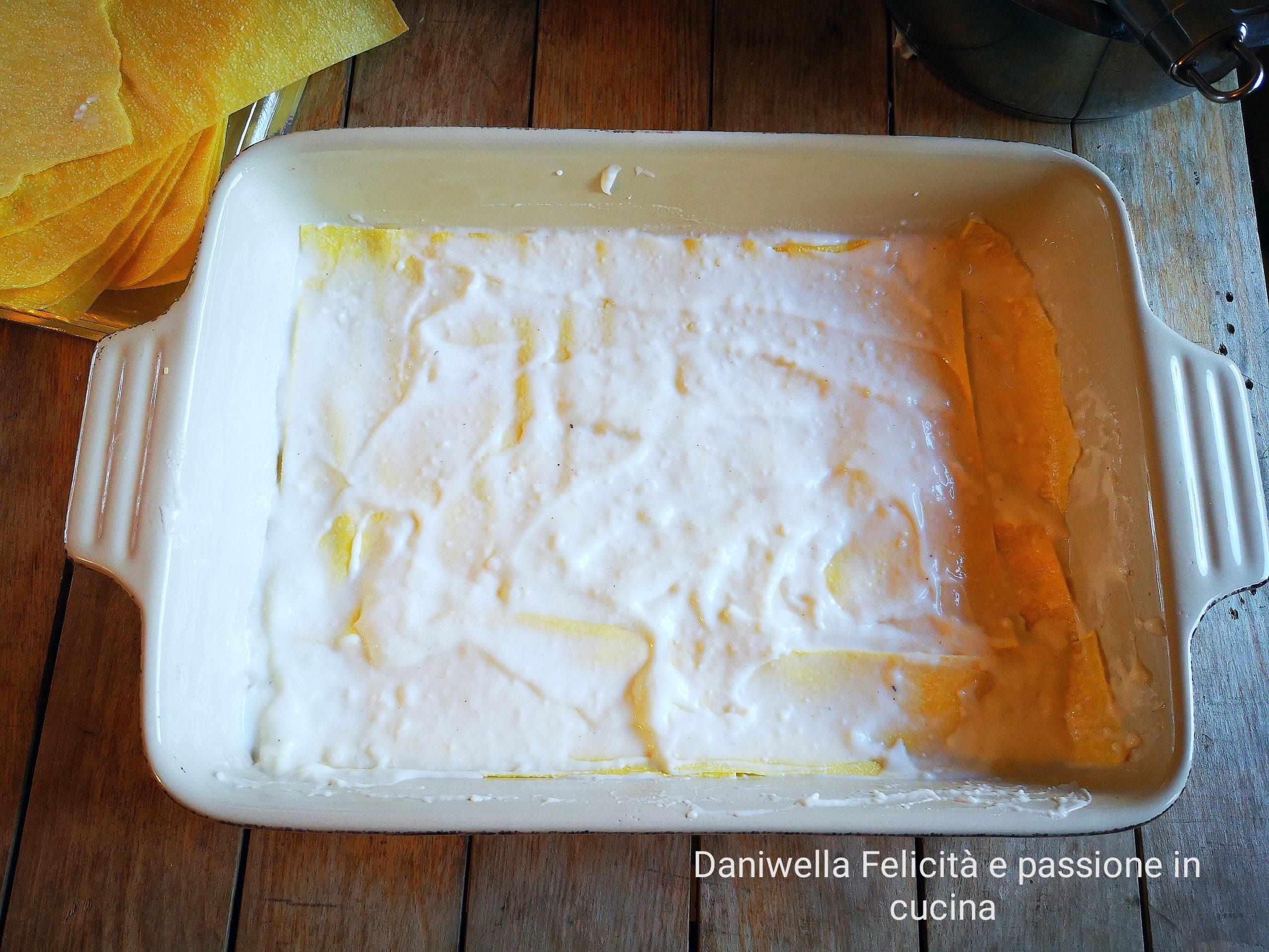 In una teglia rettangolare da 6 porzioni mettete un po' di besciamella e uno strato di lasagne. Versate sopra un'altro strato di besciamella.