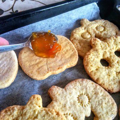Prendete le 10 basi di biscotti e riempiteli con 1 cucchiaino di confettura e con la crema spalmabile alla nocciola.