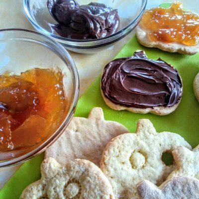 Poggiateci ora la faccina premendo leggermente per far aderire bene i due biscottini. Procedete allo stesso modo per tutti gli altri biscotti.