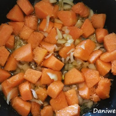 Tagliate a pezzi la zucca. Sbucciate le cipolle e tritatele finemente. Fatele appassire in una padella con 3 cucchiai di olio evo a fuoco basso per circa 10 minuti. Aggiungete la zucca a pezzi, mescolate e fate cuocere coperta fino a che diventerà morbida, ci impiegherà all'incirca 20/25 minuti.